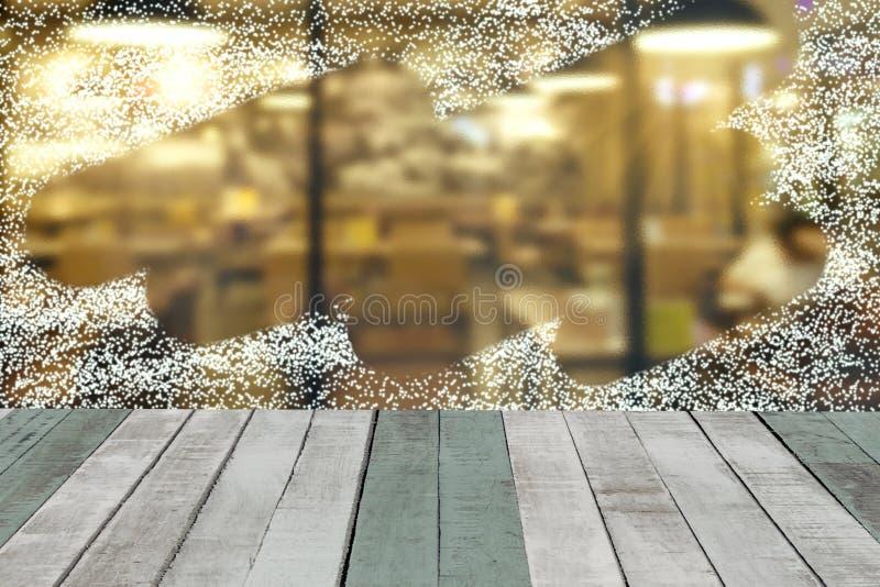 Spruzzi la neve attraverso il fondo della finestra di vetro con la tavola di legno fotografie stock