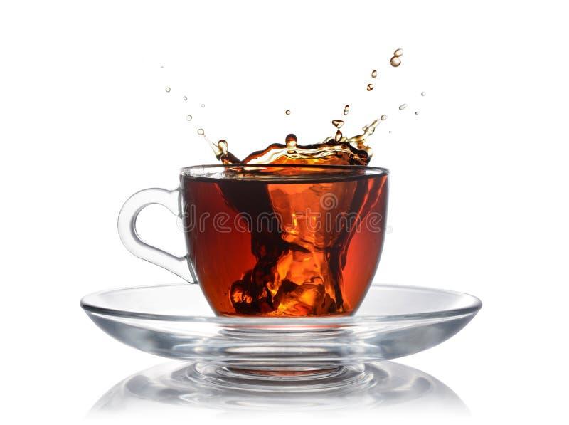 Spruzzi in tazza di vetro di tè nero con ghiaccio fotografia stock