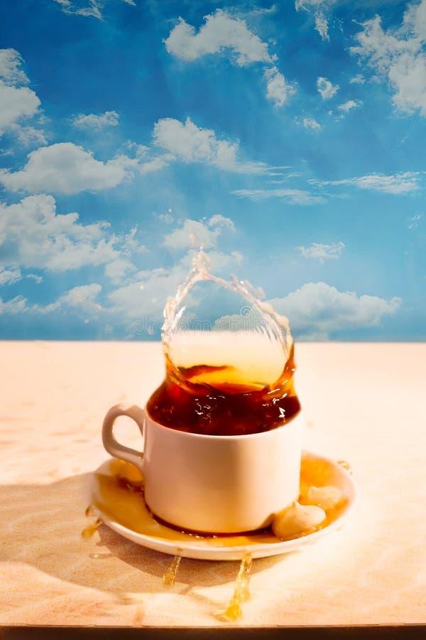 Spruzzi in una tazza di tè sui precedenti della spiaggia fotografie stock libere da diritti