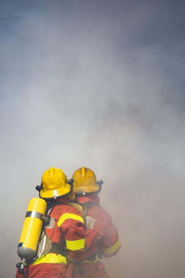 Spruzzo d'acqua di due pompieri dai wi ad alta pressione di bordi dell'ugello fotografie stock