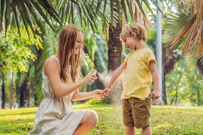 Spruzzo della zanzara di uso del figlio e della mamma Cosa repellente di insetto di spruzzatura su pelle all'aperto fotografia stock libera da diritti