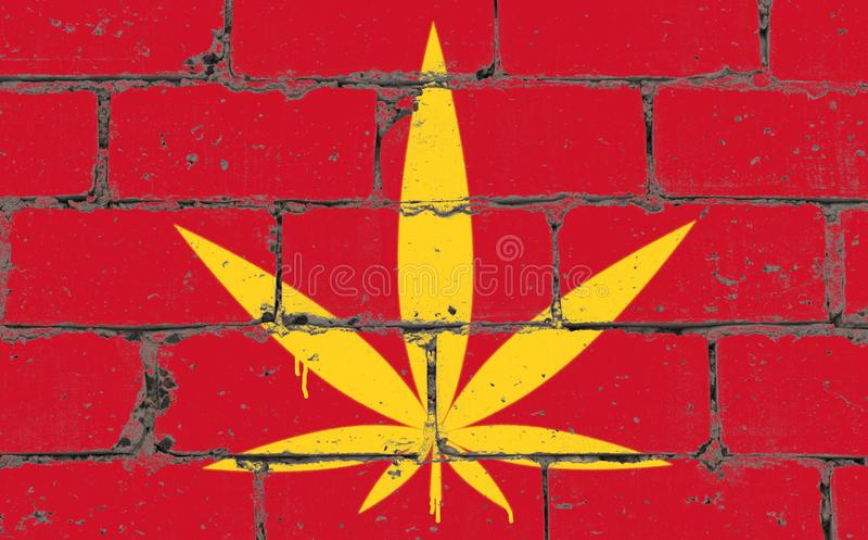 Spruzzo di arte della via dei graffiti che attinge stampino Foglia della cannabis sul muro di mattoni con la bandiera Vietnam fotografia stock