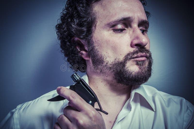 Spruzzo di pulizia, uomo con l'espressione intensa, camicia bianca immagini stock