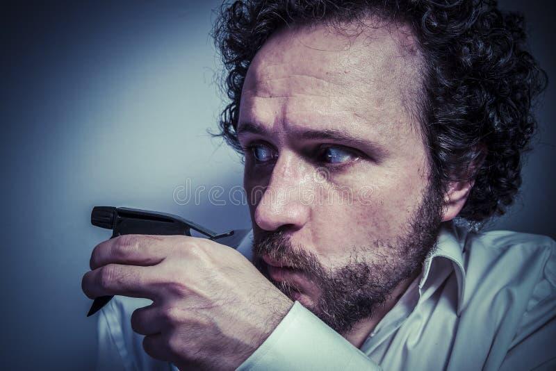 Spruzzo di pulizia, uomo con l'espressione intensa, camicia bianca fotografie stock libere da diritti