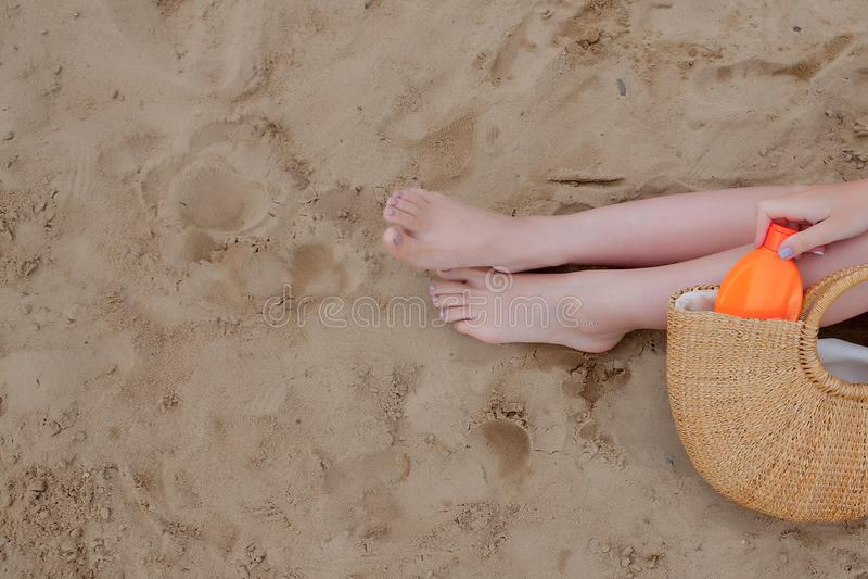 Spryskiwacz z olejem dziewczÄ™cym opalajÄ…cy nogi przed promieniowaniem sÅ'onecznym, który sprawia, że krem przeciwsÅ'oneczny bl zdjęcia stock