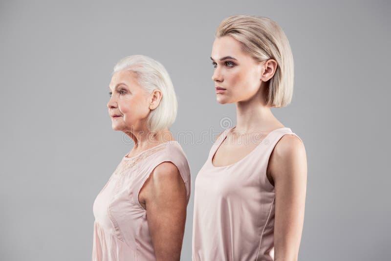 Sprząta atrakcyjne kobiety wystawia ich wzrost i starzeje się różnicy zdjęcia stock