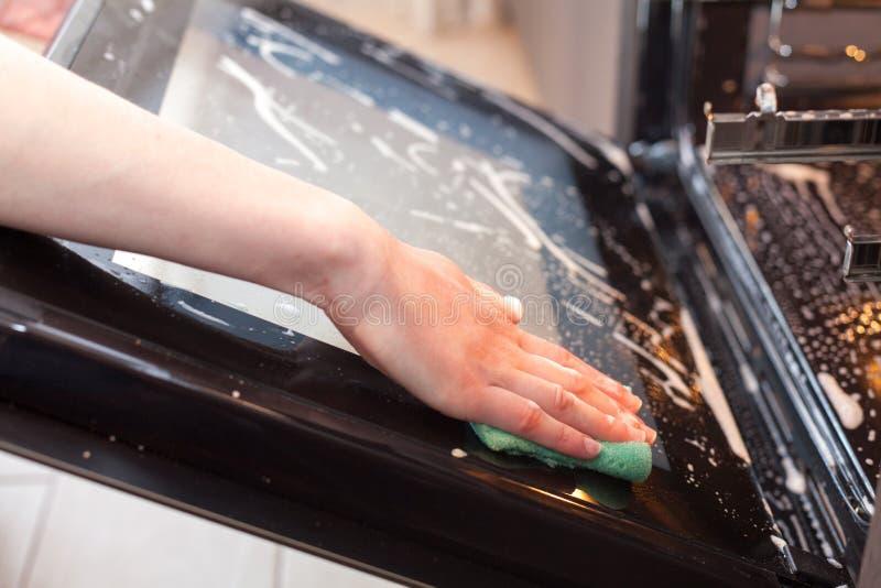Sprzątania i housekeeping pojęcie Szorować piekarnika i kuchenkę Zakończenie up żeńska ręka z zieloną gąbką czyści szklanego doo zdjęcia stock