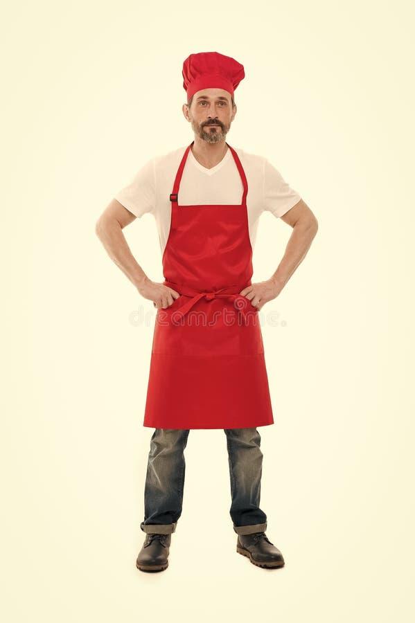 Sprz?tanie zawiera kucharstwo i czy?ci? Brodaty doro?le? m??czyzny w szefa kuchni fartuchu i kapeluszu Seniora kucharz z brod? i  zdjęcie royalty free