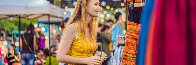 Sprzedaż, handel detaliczny, zakupy i ubraniowy pojęcie, - kobieta wybiera odzieżowego w Azjatyckim targowym sztandarze, DŁUGI fo obrazy royalty free