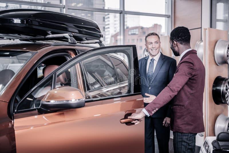 Sprzedaż kierownik jest ubranym zmrok - czerwony kurtki otwarcia drzwi samochód dla jego klienta zdjęcia stock