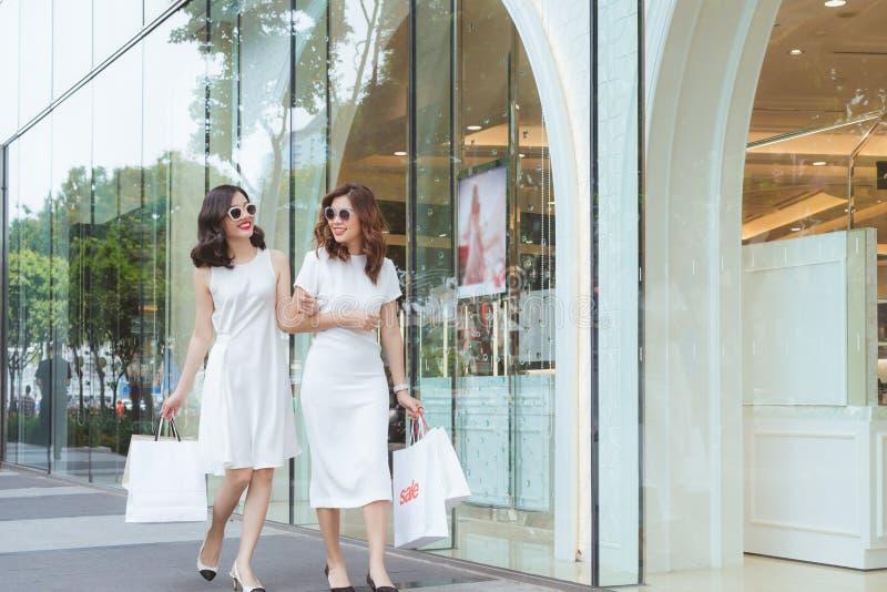 Sprzedaż, konsumeryzm i ludzie pojęć, - szczęśliwe młode kobiety z torba na zakupy na miasto ulicie fotografia stock