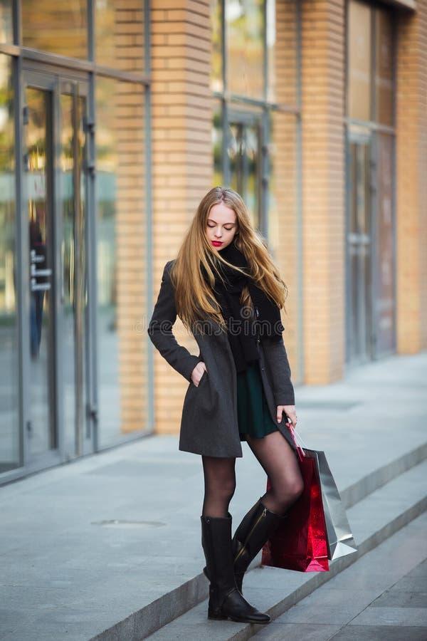 Sprzedaż, konsumeryzm i ludzie pojęć, - szczęśliwe młode piękne kobiety trzyma torba na zakupy, chodzi zdala od sklepu fotografia stock