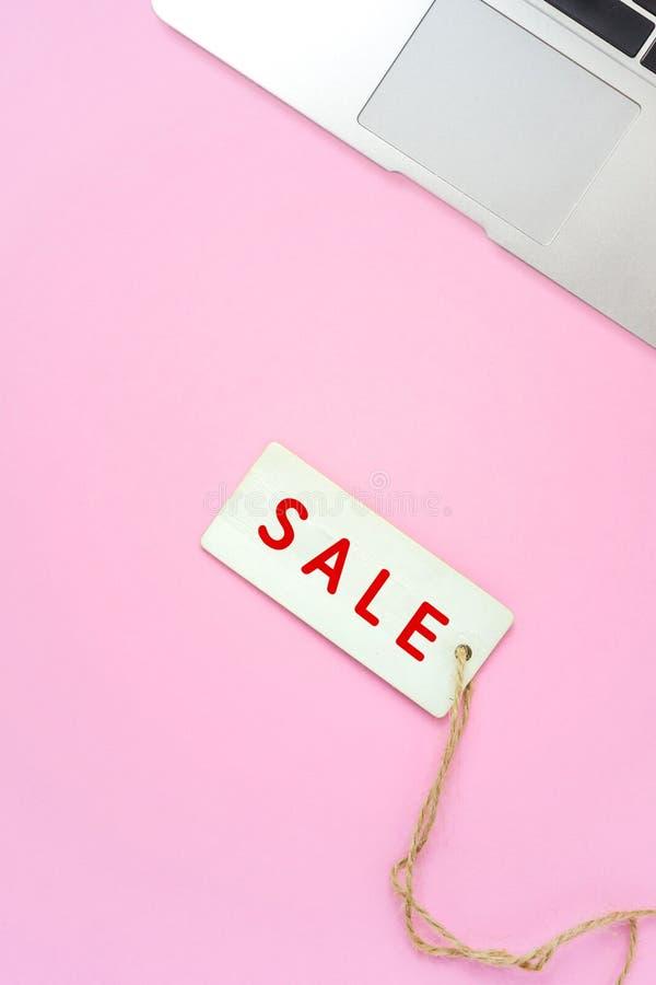 Sprzedaż laptop na różowym tle i etykietka, online zakupy zdjęcia royalty free
