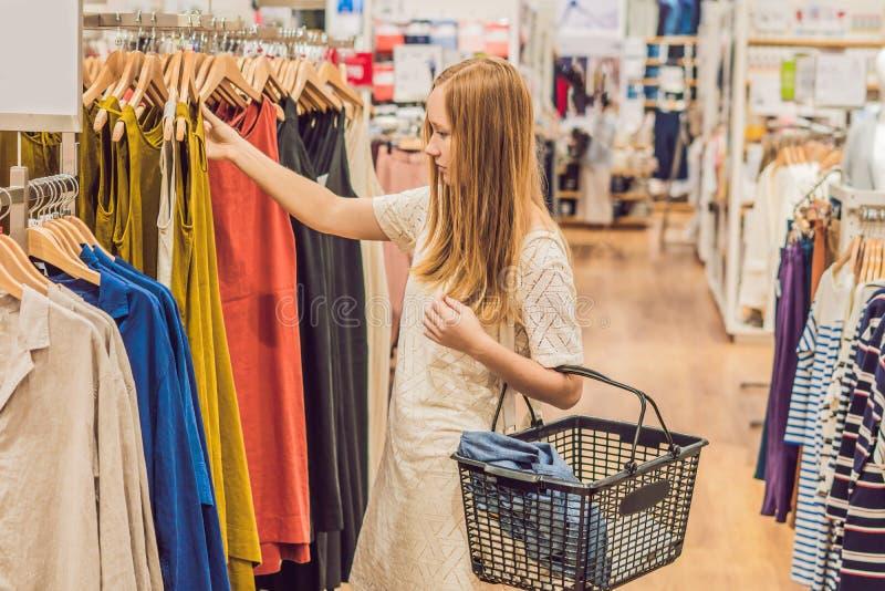 Sprzedaż, moda, konsumeryzm i ludzie pojęć, - szczęśliwa młoda kobieta z torba na zakupy wybierać odziewa w centrum handlowym lub zdjęcia stock