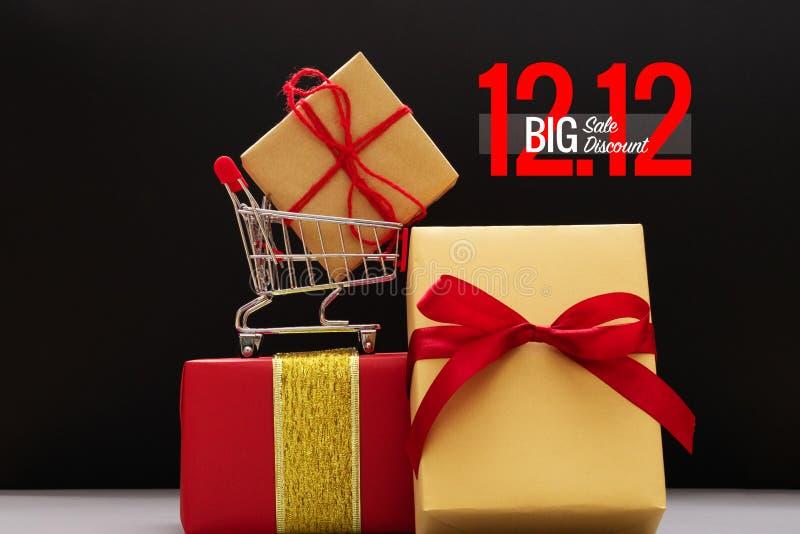 12 12 sprzedaży pojęcie, wózek na zakupy i prezenta pudełko na czarnym tle, obrazy royalty free