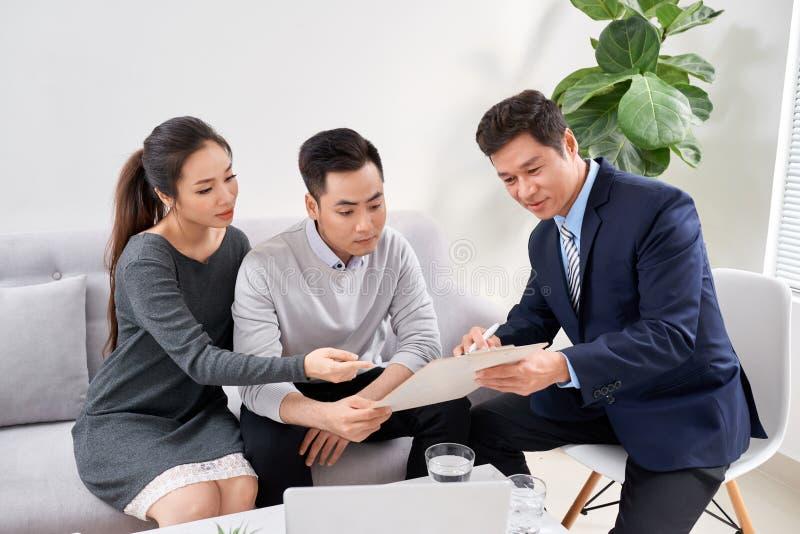 Sprzeda? konsultant pokazuje nowych inwestorskich plany m?oda azjatykcia para zdjęcia stock