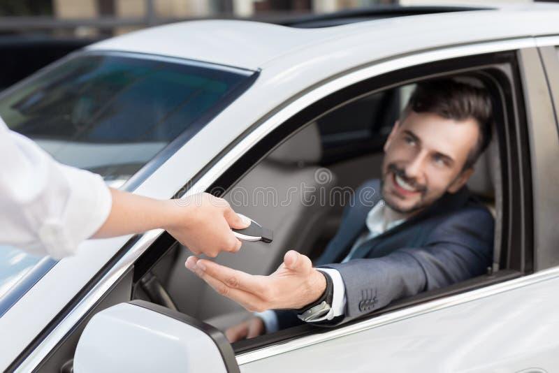 Sprzedawca daje kluczom nowy właściciel samochodu przy przedstawicielstwem handlowym zdjęcia royalty free