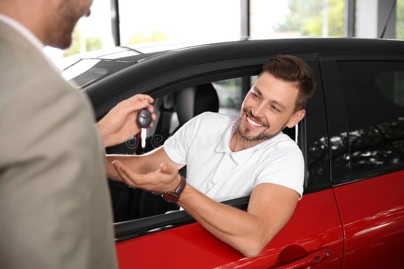 Sprzedawca daje samochodu kluczowi klient zdjęcie royalty free