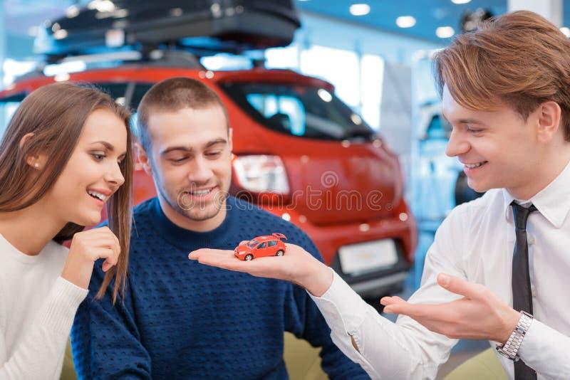 Sprzedawca demonstruje zabawkarskiego samochodu modela klienci fotografia royalty free
