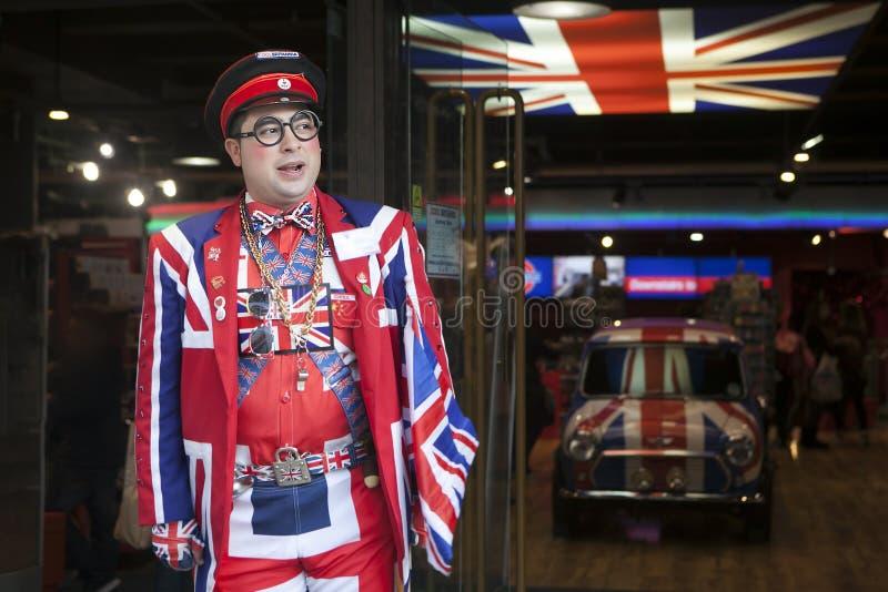 Sprzedawca jest ubranym mundur symbolizuje Angielską flaga przy wejściem sklep Chłodno Britannia fotografia royalty free