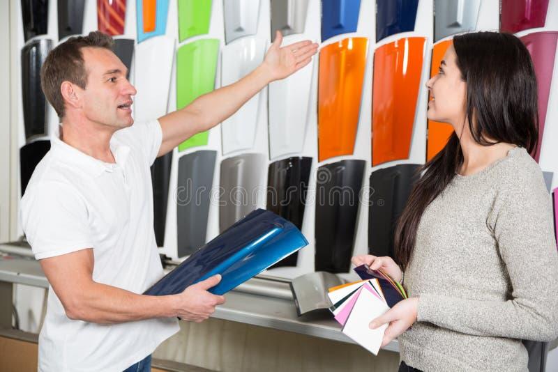 Sprzedawca konsultuje klienta o samochodowym opakowaniu udaremnia obraz stock