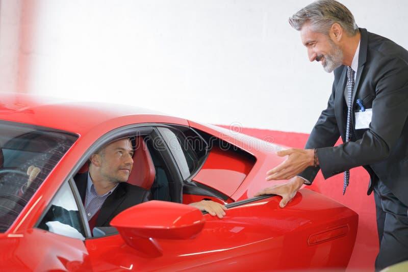 Sprzedawca pokazuje sporta samochód klient fotografia royalty free