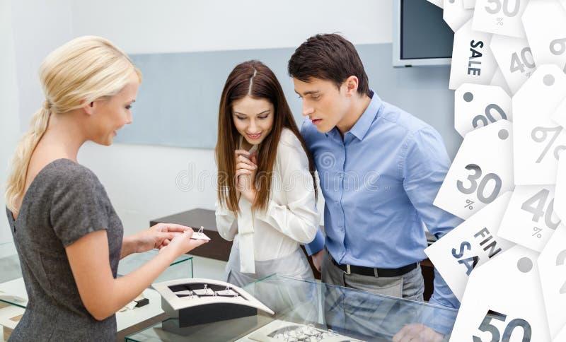 Sprzedawca pomocy para wybierać obrączki ślubne zdjęcia royalty free