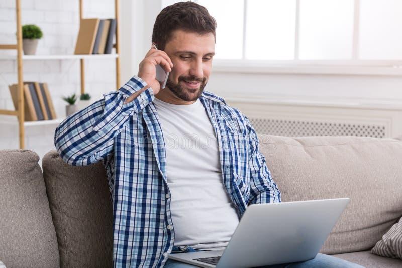 Sprzedawca pracuje w domu i opowiada na telefonie zdjęcie royalty free