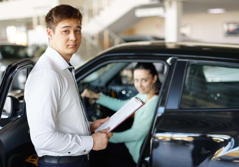 Sprzedawca przedstawia nowego samochód klienci obraz stock
