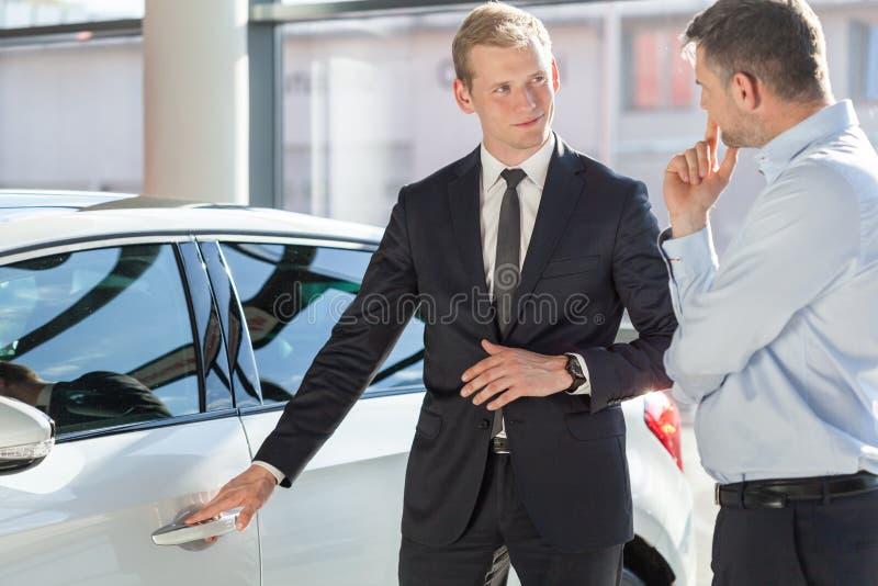 Sprzedawca przedstawia samochód klient zdjęcie stock