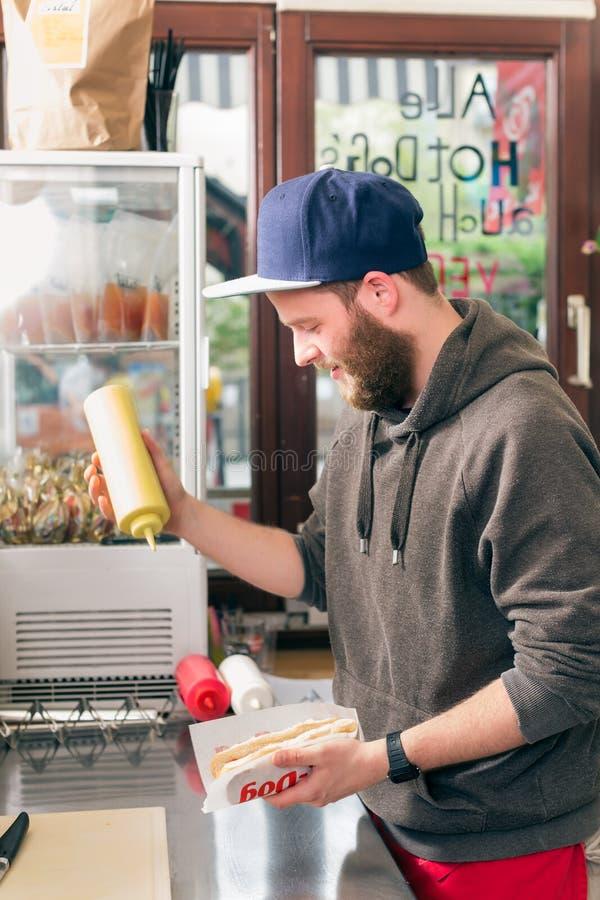Sprzedawca robi hotdog w fast food przekąski barze fotografia stock