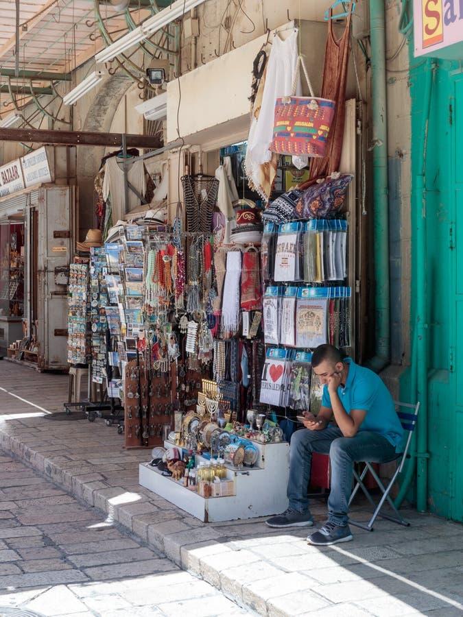 Sprzedawca siedzi blisko pamiątkarskiego sklepu w Muristan ulicie w starym mieście Jerozolima, Izrael zdjęcie stock
