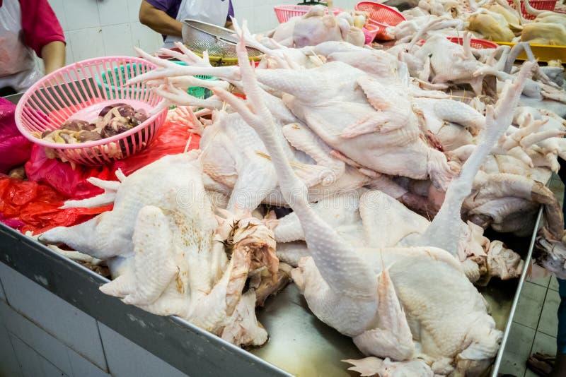 Sprzedawca sprzedaje świeżo ubitego całego kurczaka w rynku kramu zdjęcie royalty free