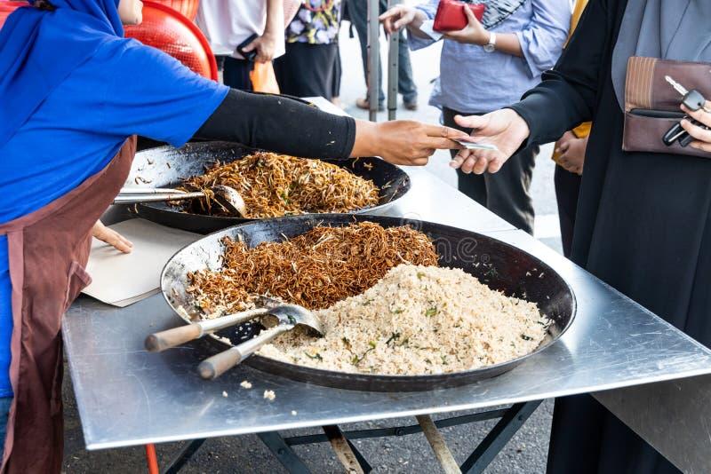 Sprzedawca sprzedaje prostego sma??cego ry?owego kluski w ulicznego rynku bazarze obrazy royalty free
