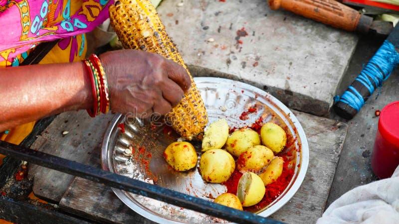 Sprzedawca uliczny naciera piec słodkiego kukurydzanego cob z cytryną i pikantność zdjęcie royalty free