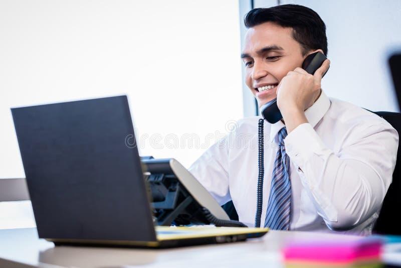 Sprzedawca w biurowej robi rozmowie telefonicza zdjęcie stock
