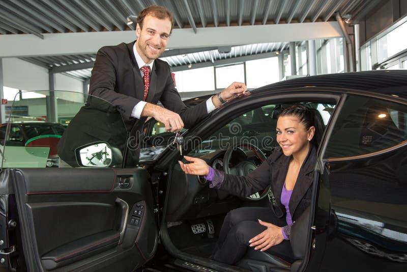 Sprzedawca w przedstawicielstwie firmy samochodowej sprzedaje samochód klient obraz stock