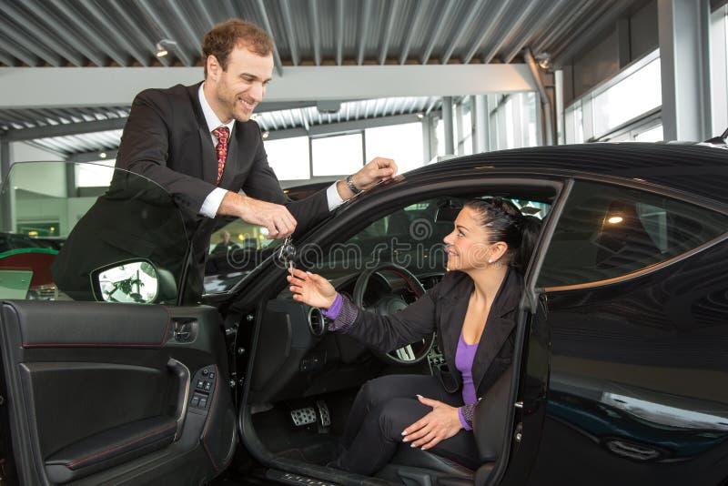 Sprzedawca w przedstawicielstwie firmy samochodowej sprzedaje samochód klient fotografia stock