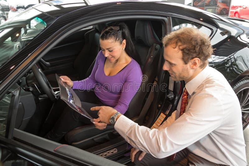 Sprzedawca w przedstawicielstwie firmy samochodowej sprzedaje samochód klient zdjęcie stock