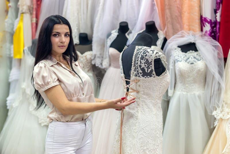 Sprzedawca w salonie ślubnym, w sukni korygującej na manekinie obraz stock