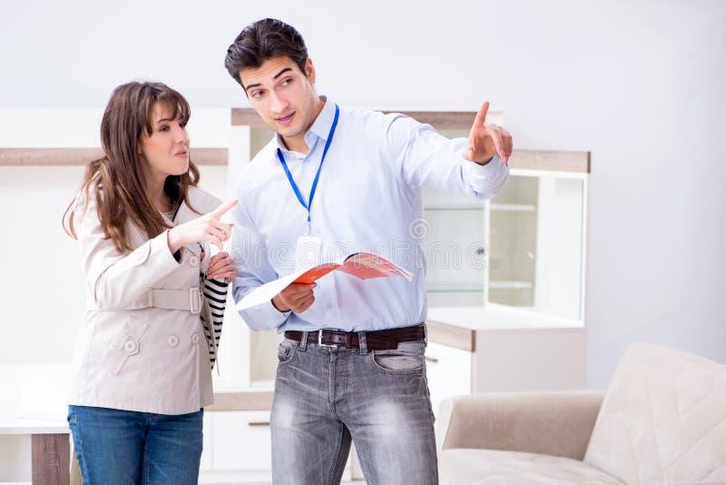 Sprzedawca wyjaśnia kobieta klient przy meblarskim sklepem zdjęcie stock