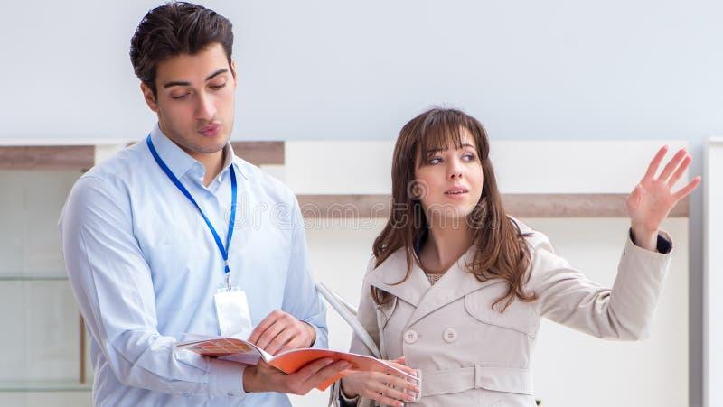Sprzedawca wyjaśnia kobieta klient przy meblarskim sklepem obraz stock