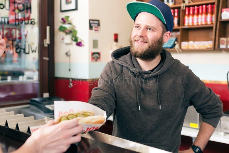 Sprzedawca z hotdog w fast food przekąski barze zdjęcie royalty free