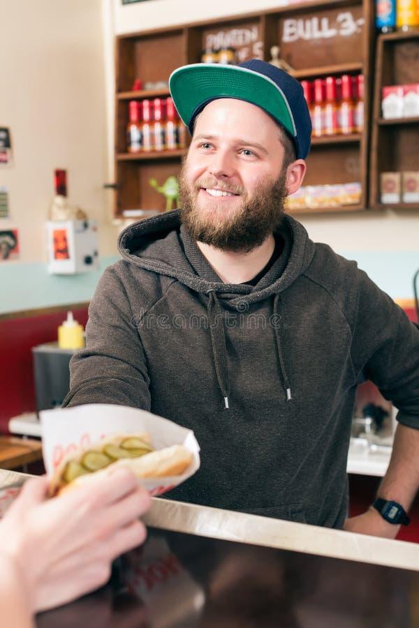 Sprzedawca z hotdog w fast food przekąski barze fotografia royalty free