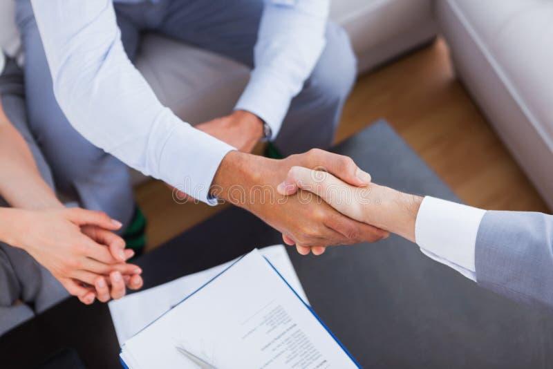 Sprzedawcy chwiania ręki z klientem obraz royalty free