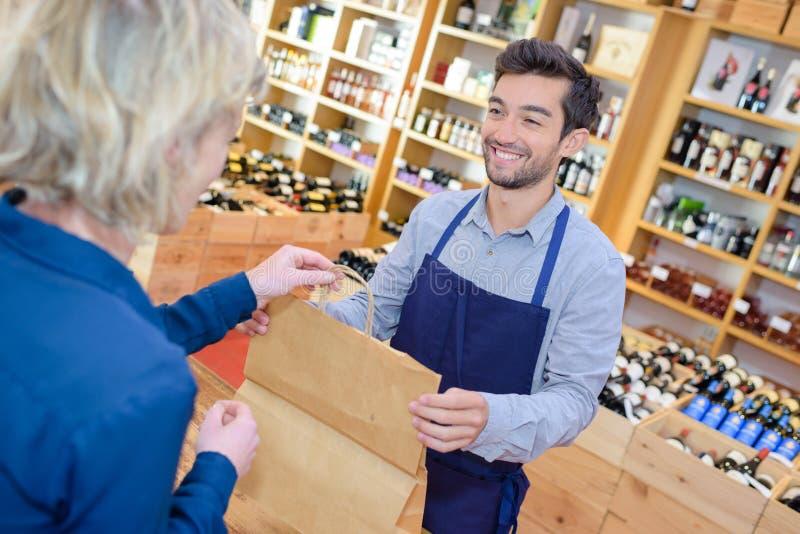 Sprzedawcy kładzenia wina butelka w paperbag dla klienta zdjęcie stock