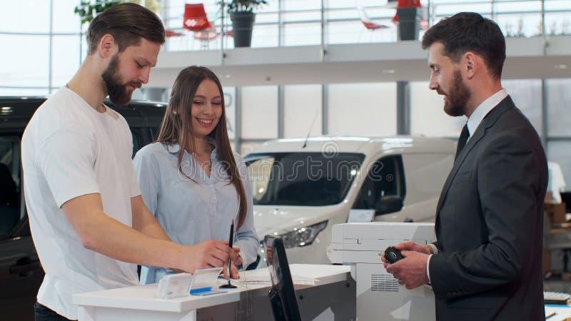 Sprzedawcy podpisywania kontrakt, daje pi?ru m??czyzna M?ody faceta k?adzenia podpis na dokumencie Sprzedawca daje kluczom samoch zdjęcie royalty free