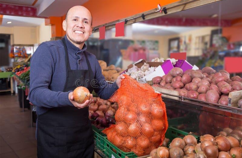 Sprzedawcy z świeżą cebulą w sklepie spożywczym obraz royalty free