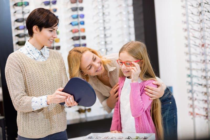 Sprzedawczyni chwyta lustro podczas gdy dziecko próby ramy dla eyeglasses fotografia royalty free