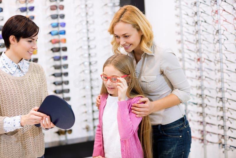 Sprzedawczyni chwyta lustro podczas gdy dziecko próby ramy dla eyeglasses zdjęcia royalty free